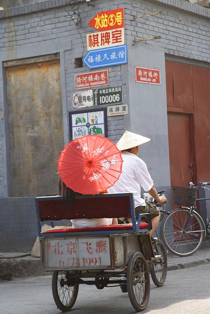 Asian woman riding in cycle rickshaw, Hutong District, Beijing, China, Asia