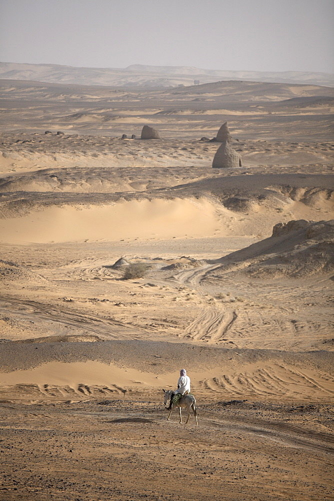 A man on mule-back traverses the desert around the ancient city of Old Dongola, Sudan, Africa - 774-150