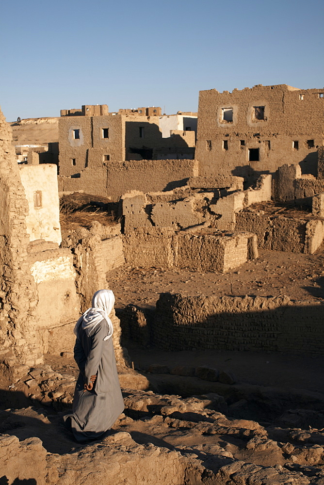 A man stands among the ruin of the mud-brick city of Al-Qasr, Dakhla Oasis, Egypt, North Africa, Africa