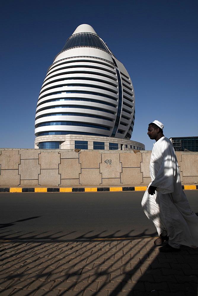 Locals walk past the 5-star Boji Al-Fateh Hotel (Libyan Hotel), designed to represent a sail, Khartoum, Sudan, Africa