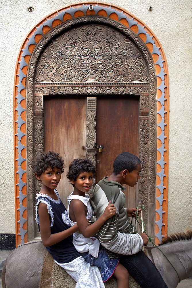 Children in front of a Lamu door, Lamu Town, Lamu, Kenya, East Africa, Africa