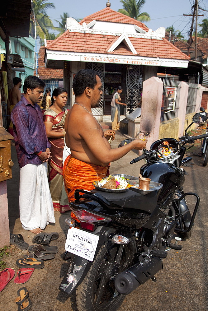 Priest blessing a new motorcycle outside a temple in Kochi (Cochin), Kerala, India, Asia