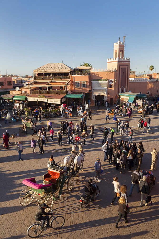 Long shadows in the busy square of Place Jemaa el-Fna, UNESCO World Heritage Site, Marrakech, Morocco, North Africa, Africa