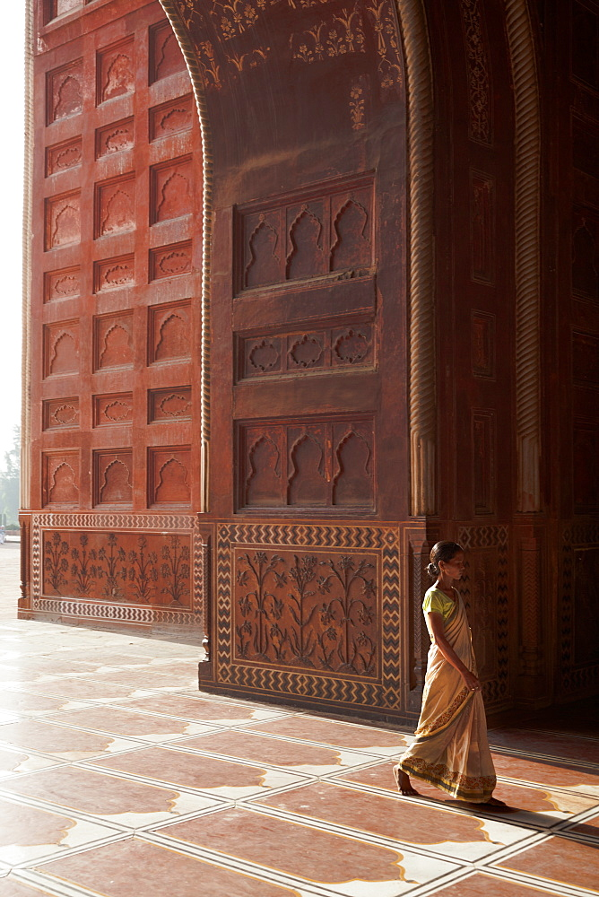 Indian lady in traditional dress walking into the mosque of the Taj Mahal, Agra, Uttar Pradesh, India, Asia