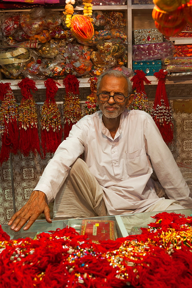 Man in shop selling traditional decorative items in Jaipur, Rajasthan, India, Asia