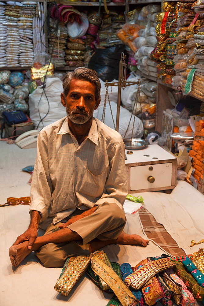 Man selling traditional belts and clothing in the city of Jaipur, Rajaasthan, India, Asia