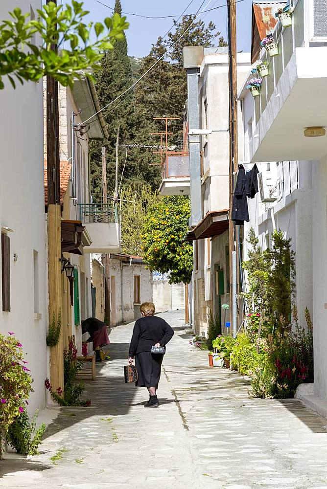 Lady in traditional dress walking in a quiet street in the historic village of Omodos in the Troodos mountains in Cyprus