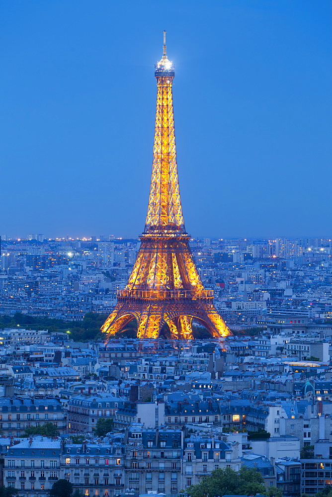 Illuminated Eiffel Tower, viewed over rooftops, Paris, France, Europe - 794-1325