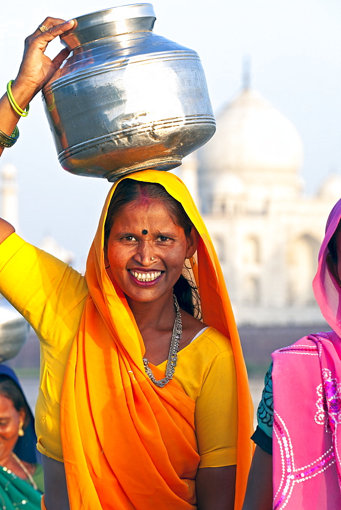 Woman carrying water pot on her head in front of the Taj Mahal, UNESCO World Heritage Site, Agra, Uttar Pradesh state, India, Asia