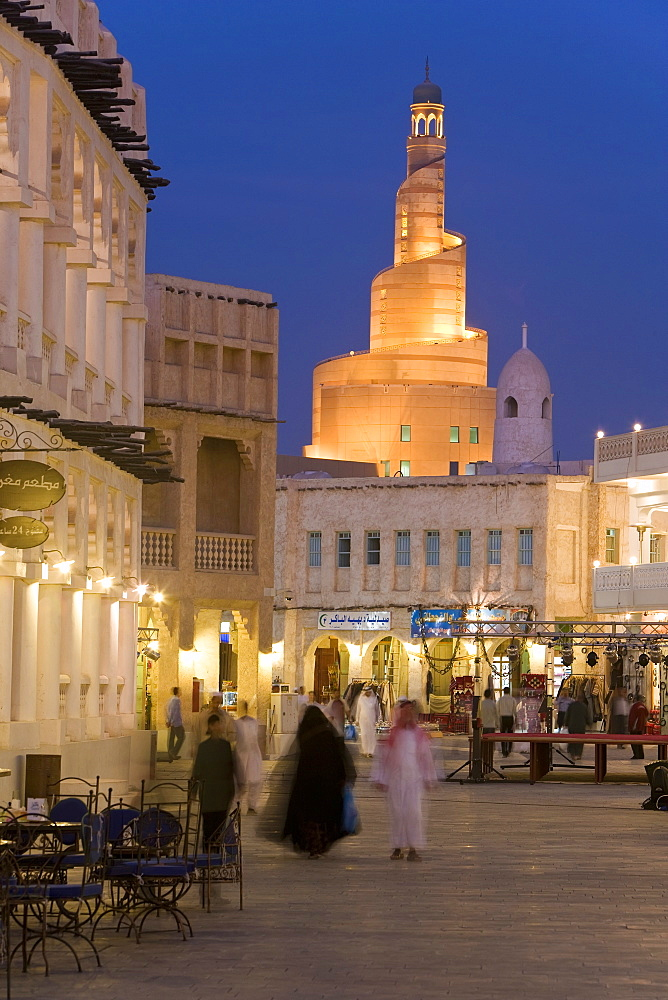 The restored Souq Waqif looking towards the illuminated spiral mosque of the Kassem Darwish Fakhroo Islamic Centre based on the Great Mosque in Samarra in Iraq, Doha, Qatar, Middle East