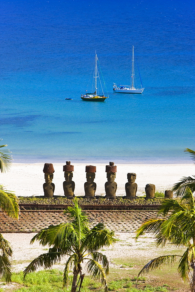 Anakena beach, yachts moored in front of the monolithic giant stone Moai statues of Ahu Nau Nau, four of which have topknots, Rapa Nui (Easter Island), UNESCO World Heritage Site, Chile, South America - 794-434