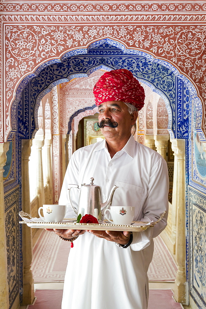 Waiter carrying tea tray in ornate passageway, Samode Palace, Jaipur, Rajasthan, India, Asia - 794-4647
