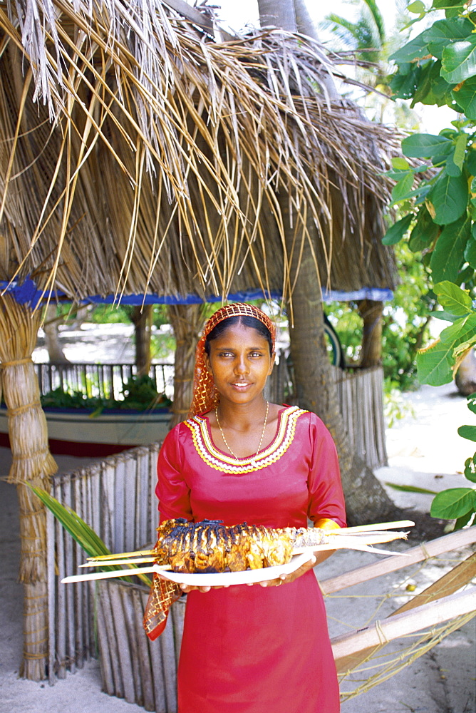 Maldivian woman offering a plate of grilled fish, Maldives, Indian Ocean, Asia