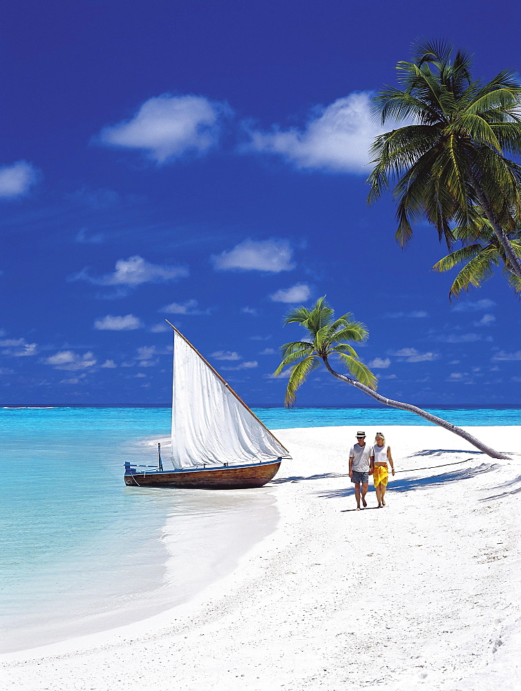 Couple walking on tropical beach and traditional dhoni, Maldives, Indian Ocean, Asia