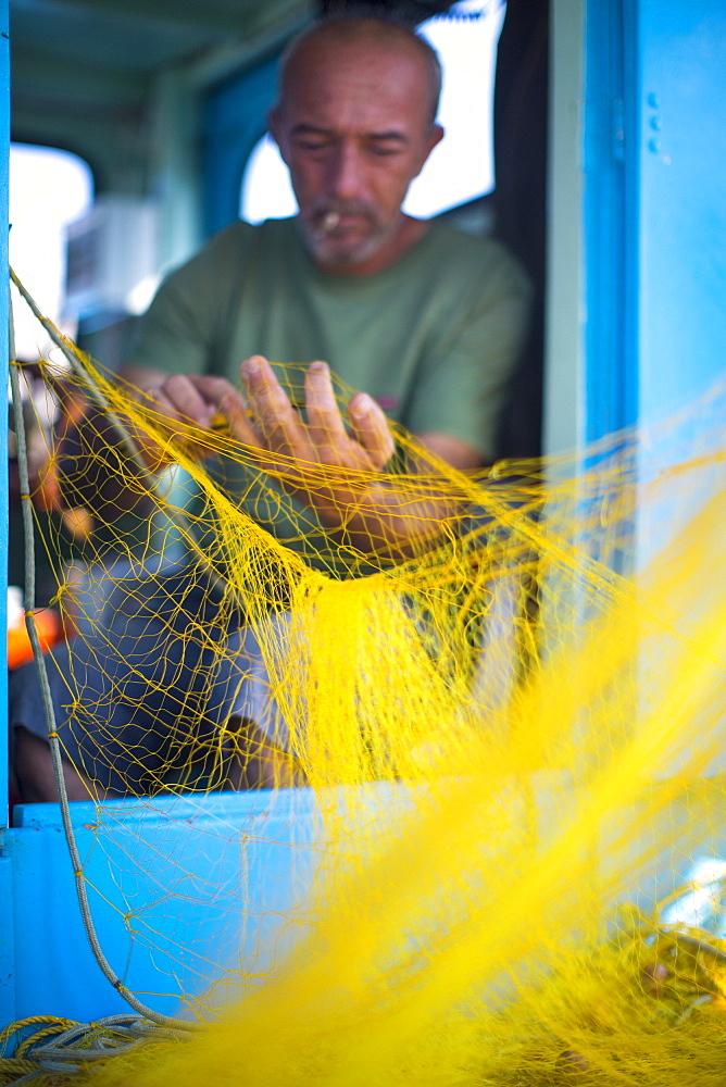 Fisherman cleaning his nets, Mykonos, Greek Islands, Greece, Europe