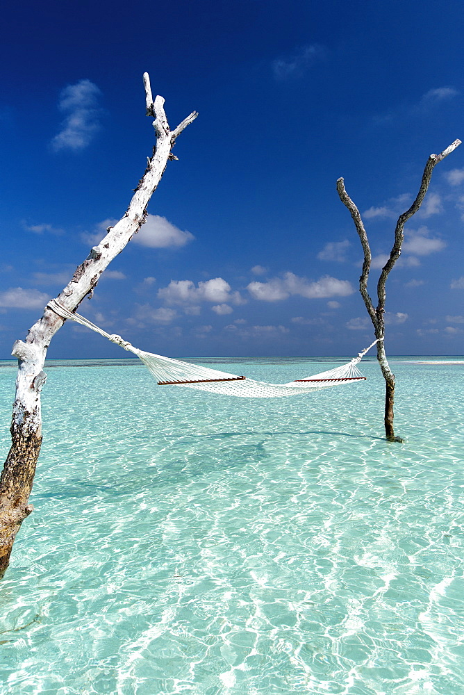 Hammock over the waters of a tropical lagoon, The Maldives, Indian Ocean, Asia