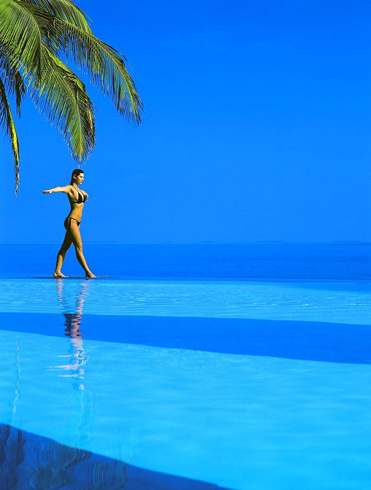 Woman balancing on edge of infinity pool, Maldives, Indian Ocean, Asia