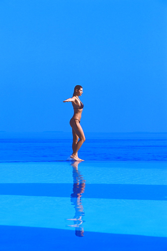 Woman walking at the Edge of Infinity pool, Maldives, Indian Ocean, Asia