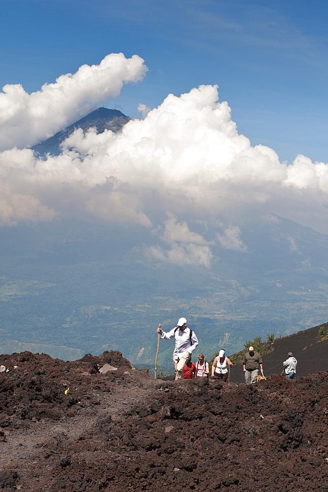 Climbing Pacaya volcano, with Fuego Volcano in distance, Antigua, Guatemala, Central America