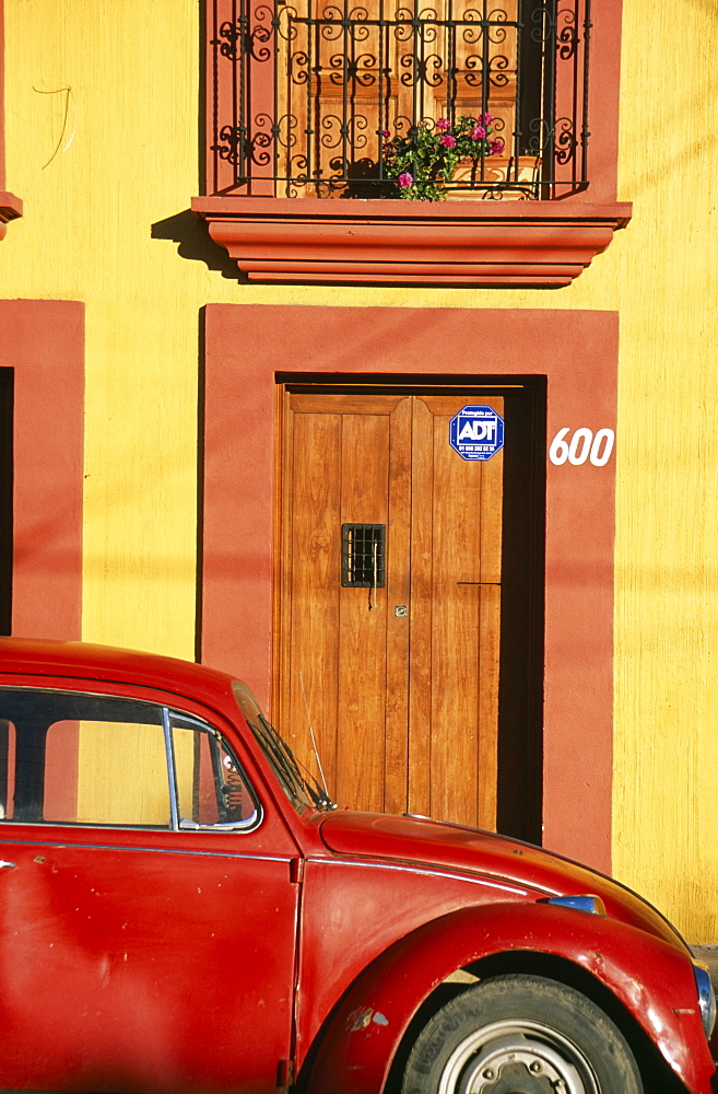MEXICO Oaxaca Oxaca City Partly seen red volkswagon beetle outside yellow building with wooden door and window shutters in orange painted frames. - 797-1024