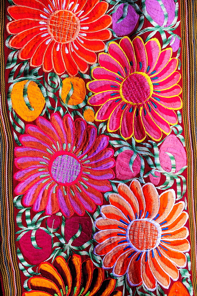 Mexico, Bajio, San Miguel de Allende, Detail of brightly coloured embroidered textile in arts shop with flower design in pink red and orange.