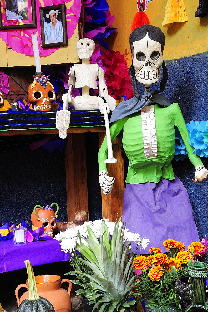 Mexico, Michoacan, Patzcuaro, Dia de los Muertos Day of the Dead altar with skeleton figures flowers and colourful paper decorations. - 797-10344