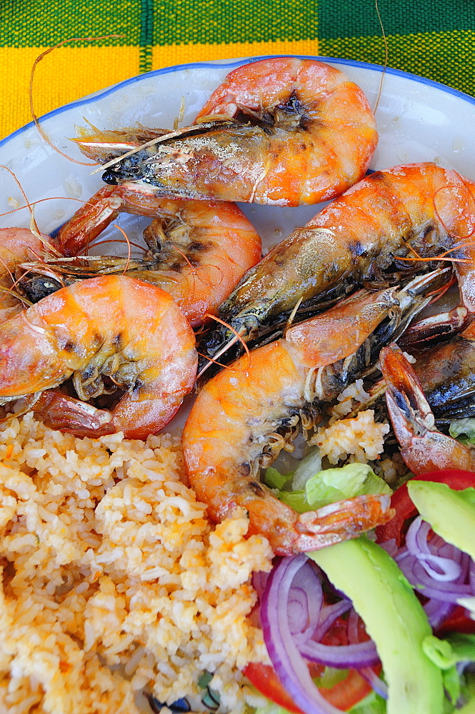 Mexico, Oaxaca, Huatulco, Gambas or prawns served on blue and white plate with sliced onion avocado tomato and couscous salad.