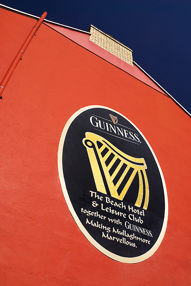 Ireland, County Sligo, Mullaghmore, Advert for Guinness on red wall of the beach hotel.