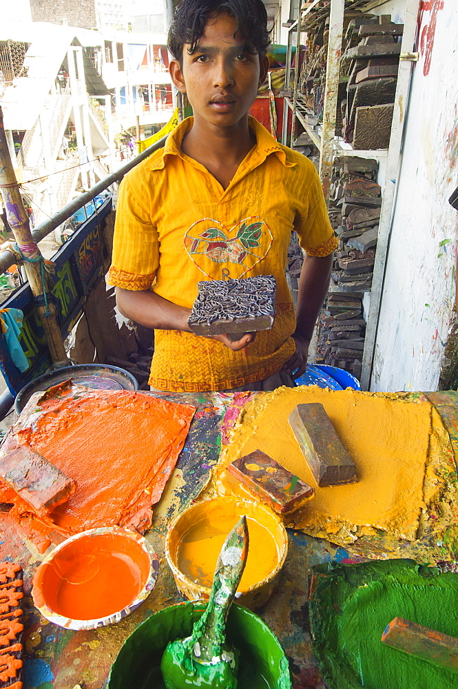 Bangladesh, Dhaka, Young man holding a printing block used to print on cotton fabrics in New Market with pallettes of colours in front of him.