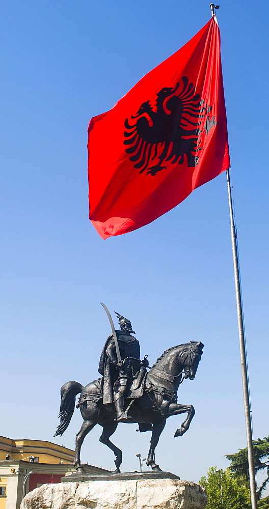 Albania, Tirana, Sculpture of National Hero Skanderbeg mounted on his horse with sword below the national flag.