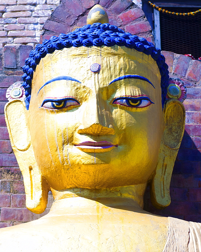 Nepal, Kathmandu, Beautiful golden Buddha head statue at theSwayambunath Monkey Temple.