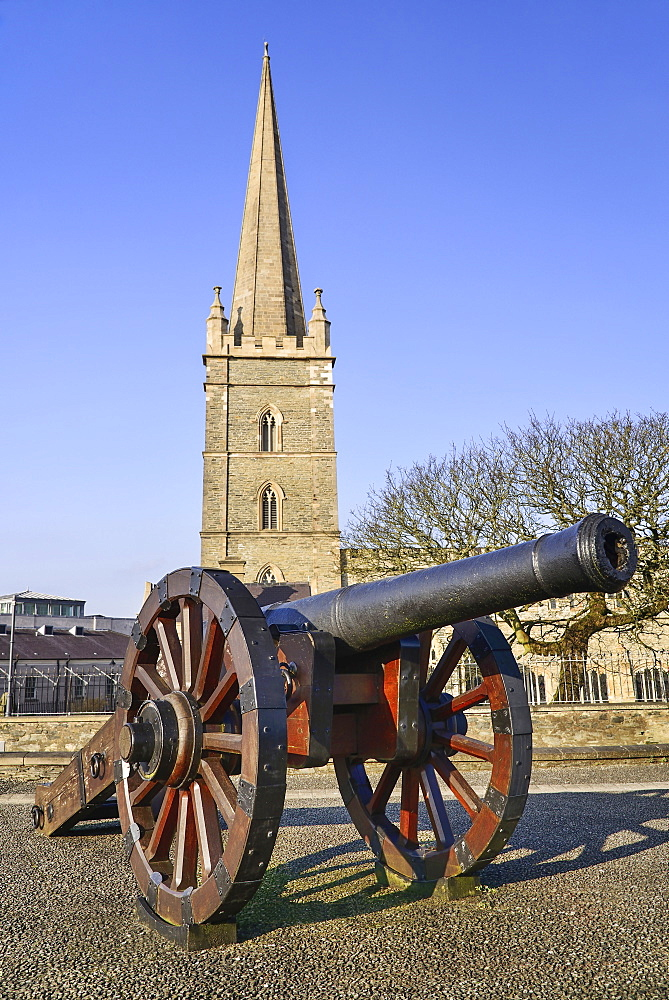 Ireland, North, Derry, St Columb's Cathedral with cannon on city walls in the foreground.