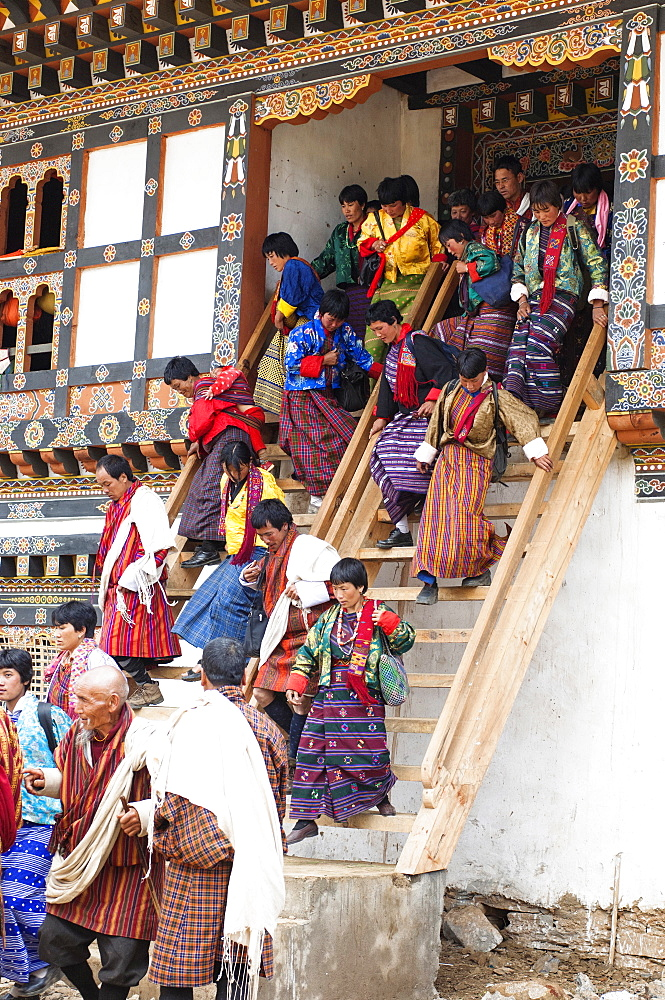 Bhutan, Gangtey Gompa, Tsecchu festival crowds descending temple steps dressed in their best clothes.
