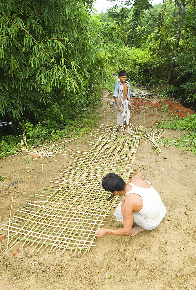 Bangladesh, Chittagong Division, Khagrachari, Two men weaving a large bamboo fence panel.