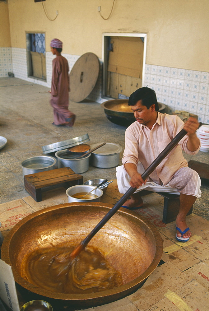 OMAN  Food  Man stirring in butter to Halva mixture