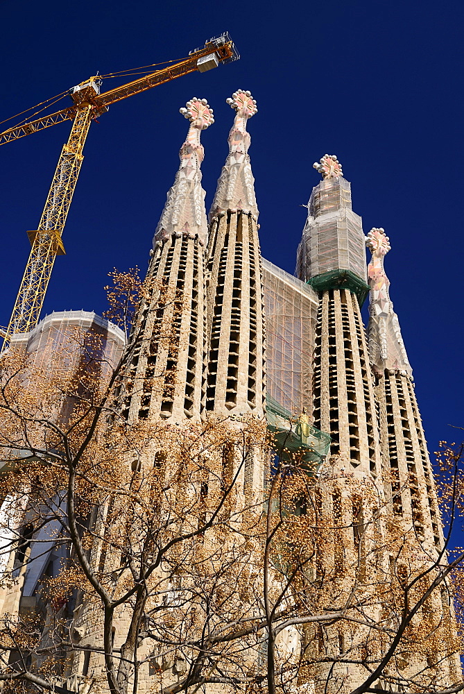 Spain, Catalonia, Barcelona, Basilica i Temple Expiatori de la Sagrada Familia, Generally known as Sagrada Familia, General view of the Passion Facade with crane hanging above.
