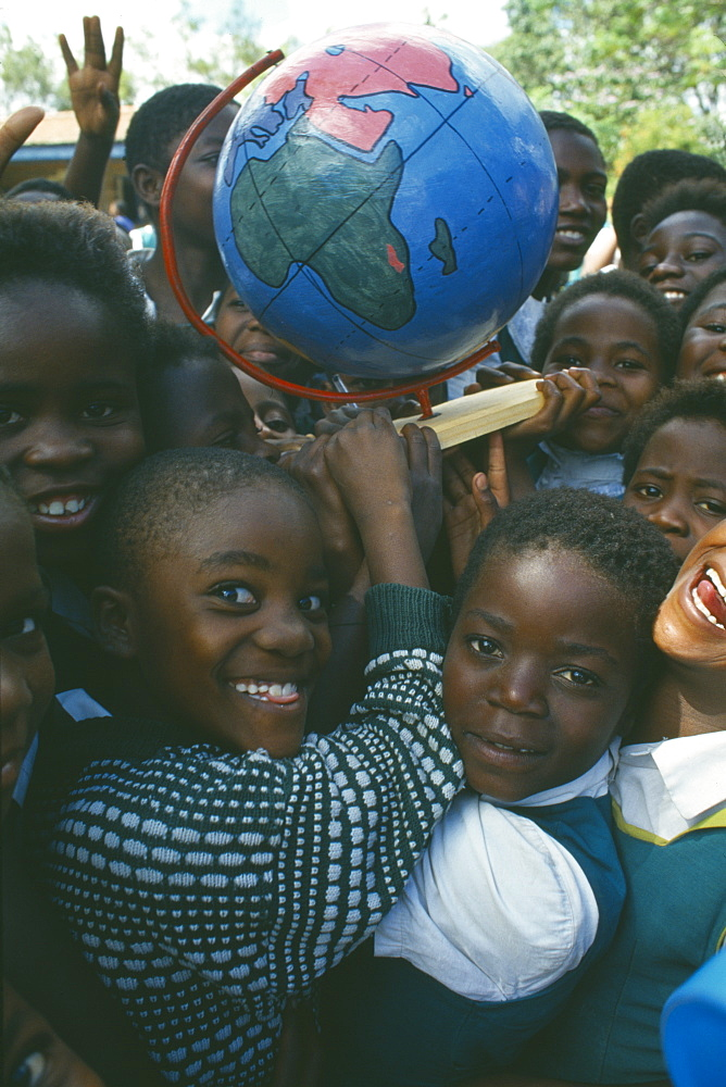 MALAWI  Blantyre School children with globe made by Pamet paper making project which produce fair trade goods from recycling everything from newspaper to elephant dung.