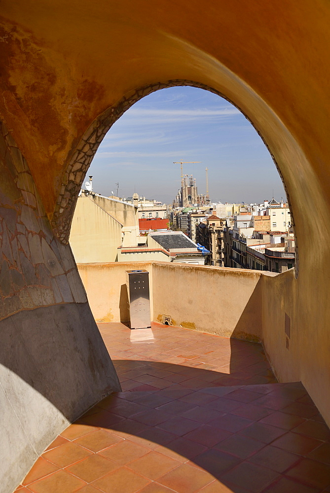 Spain, Catalunya, Barcelona, distant view of La Sagrada Familia from the rooftop of La Pedrera .