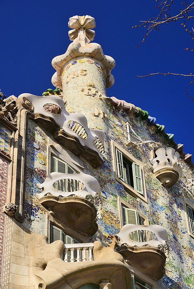 Spain, Catalunya, Barcelona, Casa Batllo by Antoni Gaudi, angular view of the upper section of the exterior facade showing window balconies and cross on roof.