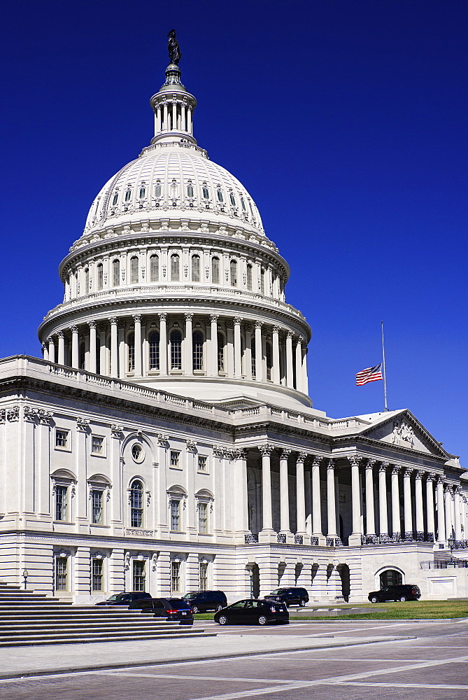 USA, Washington DC, Capitol Building, Angular view of the central section with the dome and American flag at half mast.