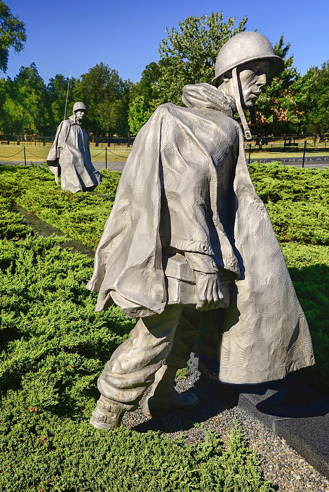 USA, Washington DC, National Mall, Korean War Veterans Memorial, Statues of soldiers on patrol in combat gear among juniper bushes.