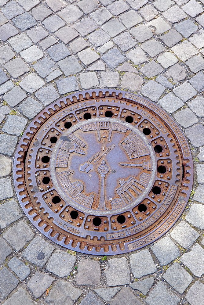 Germany, Berlin, Mitte, Museum Island, Ornately cast manhole cover showing local landmarks.