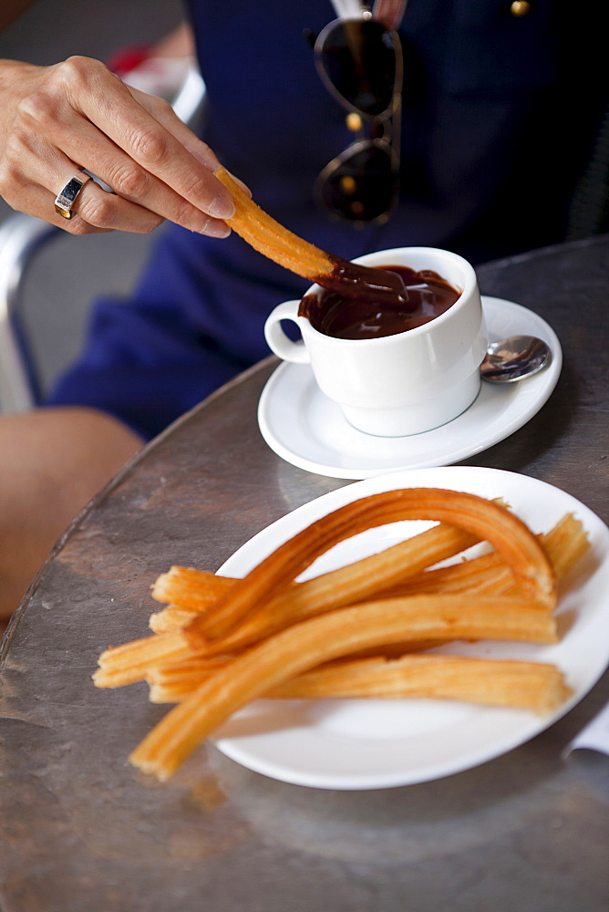 Spain, Madrid, Eating churros with hot chocolate.