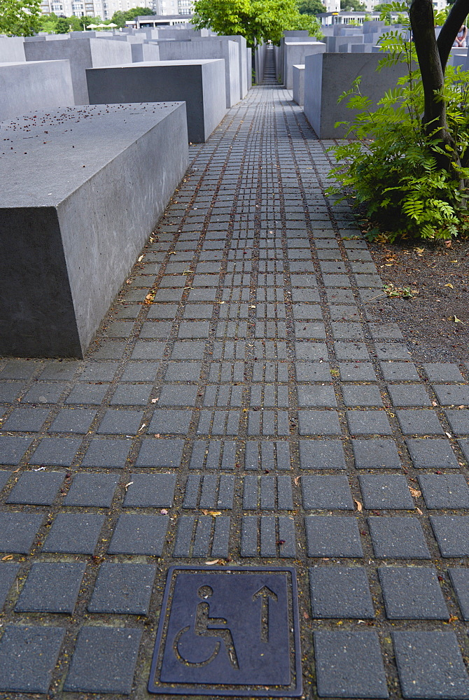 Germany, Berlin, Mitte, wheelchair access to the Holocaust Memorial designed by US architect Peter Eisenmann with a field of grey slabs symbolizing the millions of Jews killed by the Nazis.