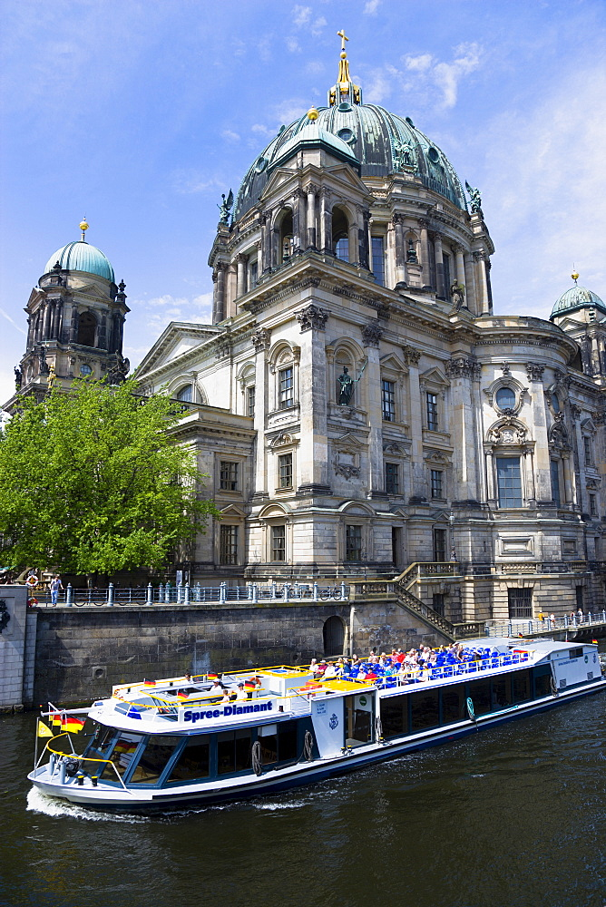 Germany, Berlin, Mitte, Museum Island. Berliner Dom, Berlin Cathedral with sightseeing tourists on a river cruise boat on the Spree.