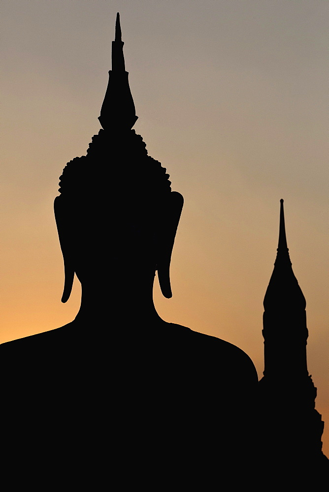 Thailand, Sukothai, Head and shoulders of seated Buddha, and tower in the background, silhouetted against sunset sky, Wat Mahathat Royal Temple.