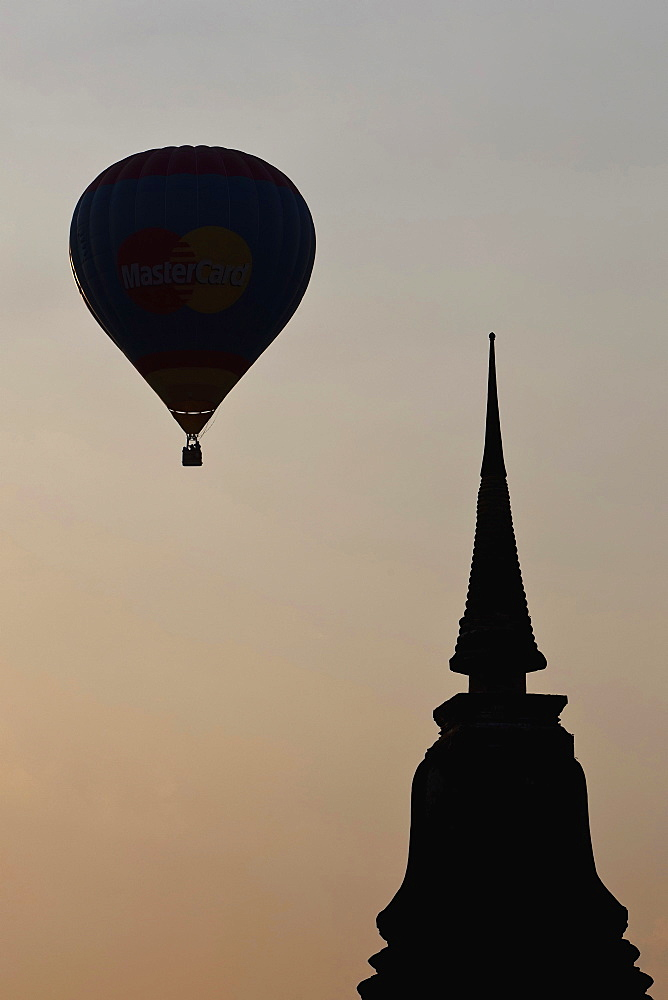 Thailand, Sukothai, Hot-air balloon and stupa top silhouetted against the sunset, Wat Mahathat Royal Temple.