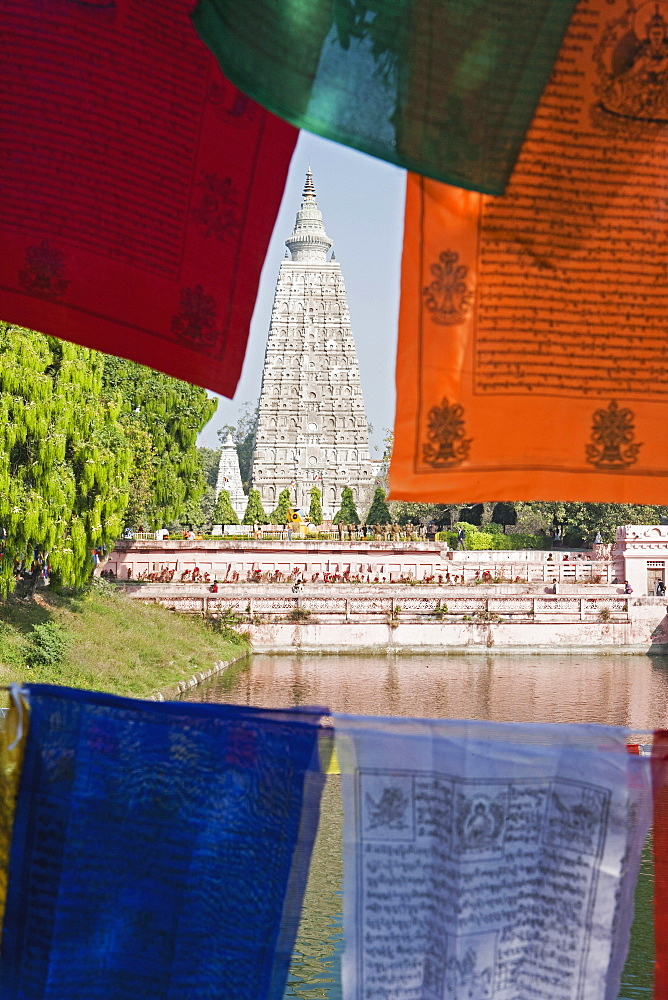India, Bihar, Bodhgaya, Mahabodhi Temple framed by colourful Buddhist prayer flags. - 797-12869