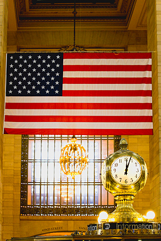 USA, New, York, Manhattan, The Central Information four sided clock in Grand Central Terminal main concourse with the Stars and Stripes flag hanging down from the ceiling behind. - 797-12929