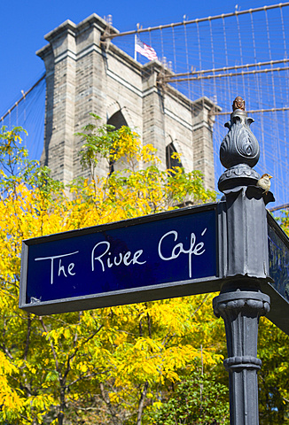 USA, New York, Brooklyn Bridge Park, signpost for The River cafe and detail of one of the suspension bridge towers against a blue sky in autumn colours.